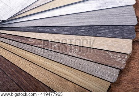 Vinyl And Linoleum Samples On A White Isolated Background. Vinyl For Flooring With Wood Grain Textur