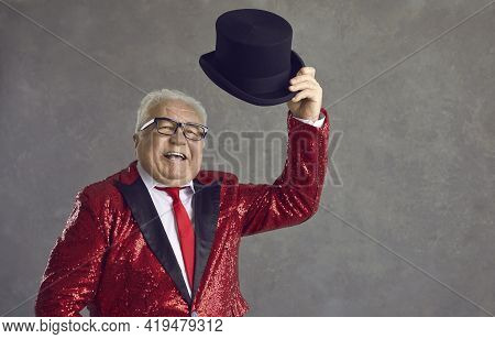 Happy Senior Presenter In Red Sequin Jacket Takes Off His Black Top Hat And Greets Audience