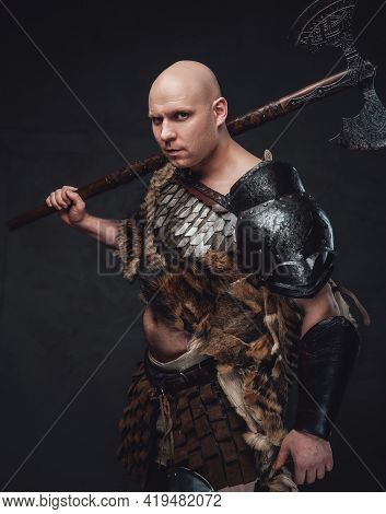 Hairless Ancient Warrior Holding Axes Against Dark Background