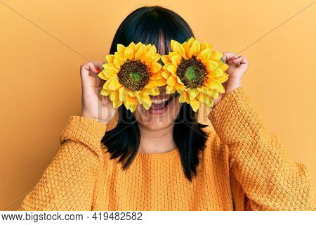 Young hispanic woman holding sunflowers over eyes smiling and laughing hard out loud because funny crazy joke.