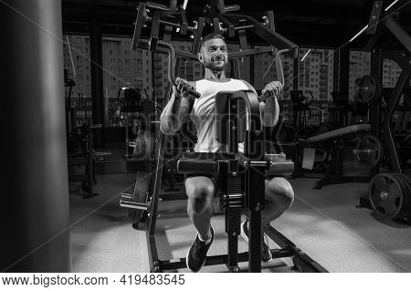 Handsome Young Man Pumps His Shoulders In A Special Machine. Fitness And Bodybuilding Concept.