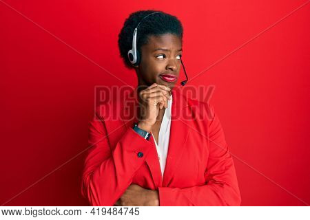 Young african american girl wearing call center agent headset serious face thinking about question with hand on chin, thoughtful about confusing idea