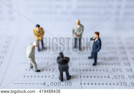 Business Financial And Teamwork Concept. Group Of Businessman Miniature Figures People Standing On B