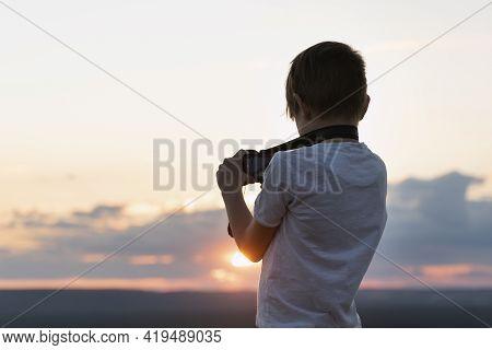 Boy Photographs The Sunset. Child With Camera On Setting Sun Background