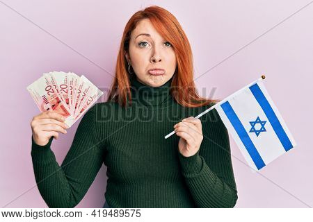 Beautiful redhead woman holding 20 shekels banknotes and israel flag depressed and worry for distress, crying angry and afraid. sad expression.