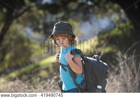 Kids With Backpack Hiking. Boy Child Local Tourist Goes On A Local Hike.