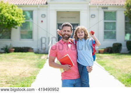 American Father And Son Walking Trough School Park. Portrait Of Teacher And Happy Pupil.