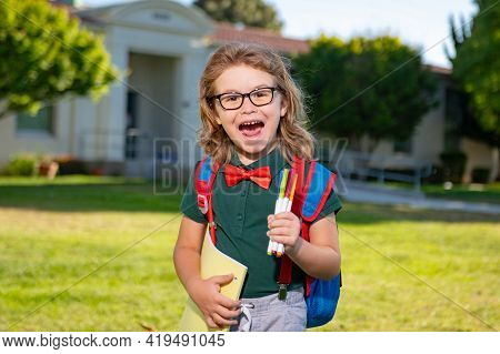 Excited School Student With Backpack And Book. Portrait Of Pupil Outside The Primary School. Closeup