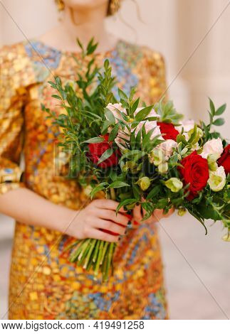 A Bride In An Unusual Golden Dress Holds A Bridal Bouquet Of White And Red Roses In Her Hands, Close