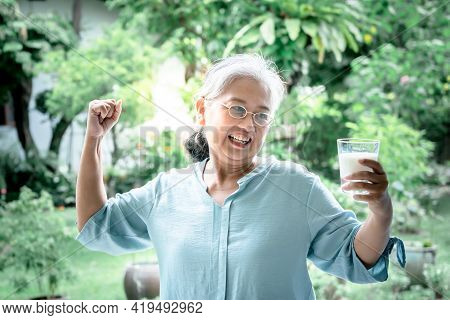 An Asian Elderly Woman, Happy And Showing Her Strength In Good Health, And Holding A Glass Of Milk W