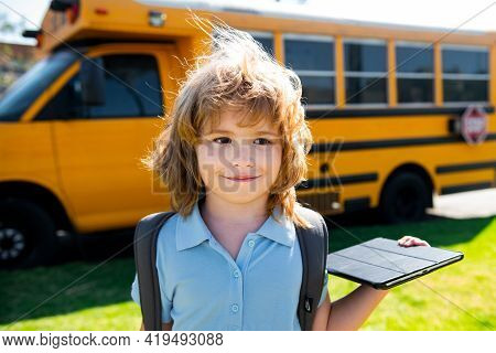 Pupil Kid With Tablet Near School Bus. Social Distance During Quarantine, On-line Education Concept,