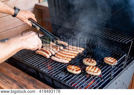 Chef Preparing Meat On The Grill, During Outdoor Outside Food Festival, Food Truck, Brunch Or Cateri