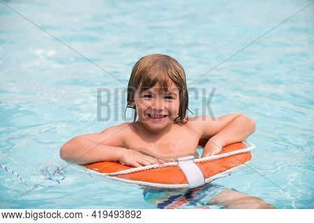 Child In Summer Pool. Summer Kids Weekend. Happy Boy In Swiming Pool On Inflatable Circle At Aquapar