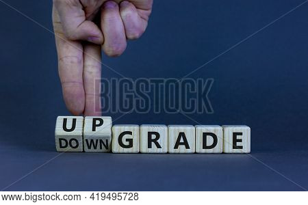 Upgrade Or Downgrade Symbol. Businessman Turns Wooden Cubes And Changes Words 'downgrade' To 'upgrad