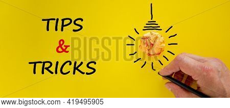 Tips And Tricks Symbol. Businessman Writing Words 'tips And Tricks', Isolated On Beautiful Yellow Ba