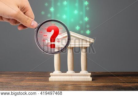 A Hand With A Magnifying Glass Inspects Bank And Finds Financial Violations. Audit And Accounting. M
