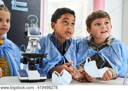 Waist Up Portrait Of The Curious Children Listening Chemistry Lesson