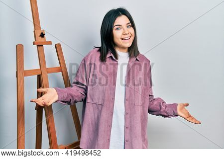 Young brunette woman standing by empty easel stand celebrating achievement with happy smile and winner expression with raised hand