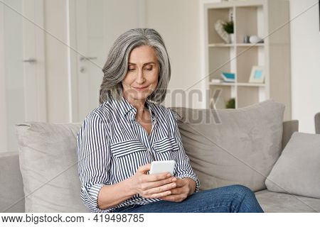 Happy Mid Age Senior Adult Woman Using Smartphone Sitting On Sofa At Home. Relaxed Mature Older Lady