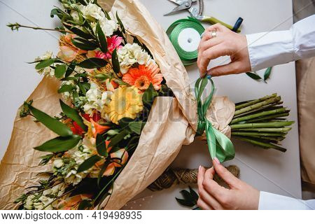 A Female Florist Ties A Green Ribbon Bow On A Bouquet Of Flowers Wrapped In Craft Paper On The Deskt