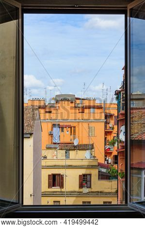 Rome, Italy, August 2014: Typical natural aout of window view to usual old residential buildings with tile rooftops in Rome, Italy