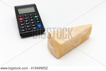 A Piece Of Cheese Wrapped In Polyethylene, Cash Register. Cheese Is Triangular On The The White Back