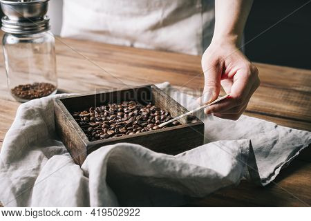 Hand Scooping Coffee Beans With A Wooden Spoon Into A Square Wooden Container
