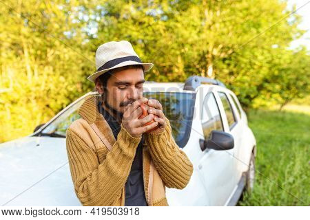Hispanic Man Enjoying A Cup Of Coffee Leaning On His Off-road Suv Car In The Middle Of Nature. Weeke