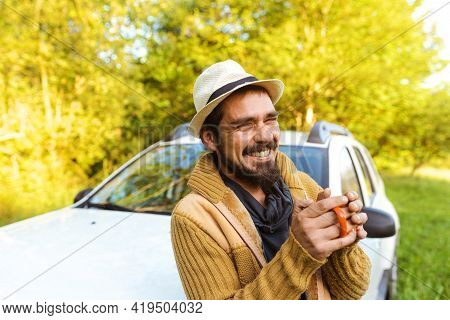 Latino Young Man In Sombrero Laughing While Enjoying A Cup Of Drink Leaning On His Off-road Suv Car.