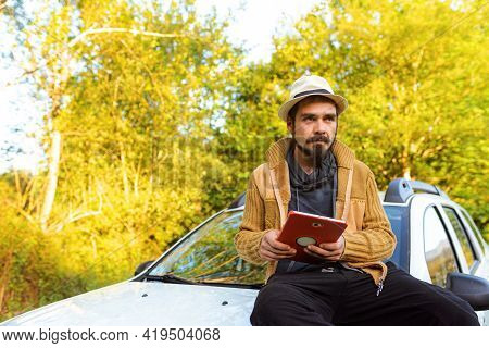 Young Hispanic Man Holding And Using A Tablet Sitting On The Hood Of His Car In The Middle Of Nature