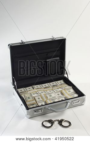 Silver suitcase full of dollars and handcuffs, studio shot