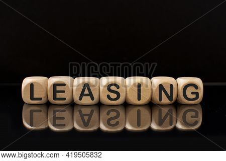Wooden Blocks With The Word Leasing With A Reflection On A Black Background .