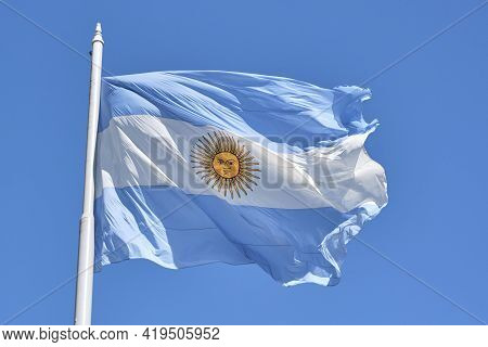 Argentine Flag Flying On A Flagpole Against A Blue Sky On A Sunny Day. Patriotic Symbol Of Argentina