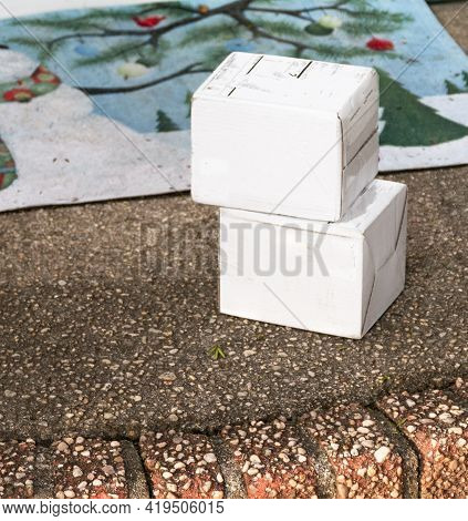 Two Small White Packages Delivered To A Front Stoop Left Out Exposed To The Elements And Thieves.