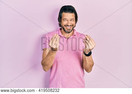 Middle age caucasian man wearing casual white t shirt doing money gesture with hands, asking for salary payment, millionaire business