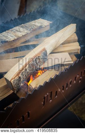 Dry wood in the grill for kindling and making coals