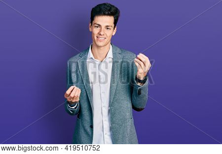 Young hispanic man wearing business clothes doing money gesture with hands, asking for salary payment, millionaire business