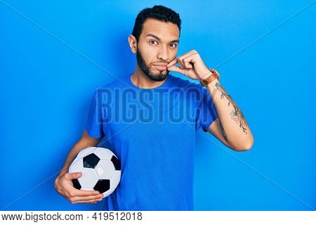 Hispanic man with beard holding soccer ball mouth and lips shut as zip with fingers. secret and silent, taboo talking