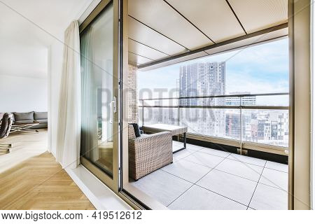 Cozy Sofa And Wooden Table Placed On Balcony Of Apartment Building With Cityscape View