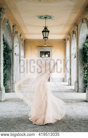 Bride In A Wedding Dress Stands Covered Herself With A Veil On An Old Pillared Terrace. Lake Como