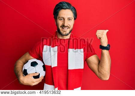 Young hispanic man football hooligan holding ball pointing thumb up to the side smiling happy with open mouth