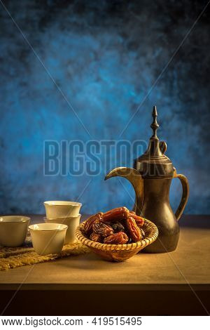A still life of Arabic traditional coffee pot or Dallah along black coffee served with sweet dates. A rustic set up of a beverage serving at Mazleej.