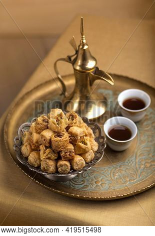A platter of Baklava - a Turkish sweet served with Arabic black coffee. Middle Eastern authentic dessert and beverage. Arabic hospitality with a traditional coffee and sweet.