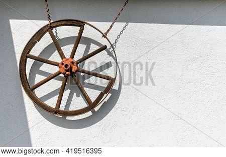 Old Decorative Wheel On A White Wall, Nostalgia Style