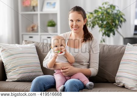 family, motherhood and people concept - happy smiling mother and little baby playing with teething toy or rattle at home