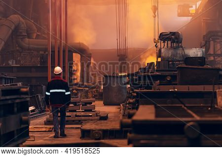 Worker Inside Steel Metallurgical Factory Or Foundry Workshop Interior, Heavy Industry Concept.