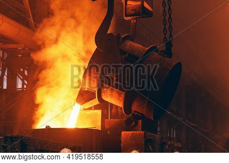 Molten Metal Pour From Big Container Into Sand Mold With Sparks. Iron Casting In Metallurgy Foundry
