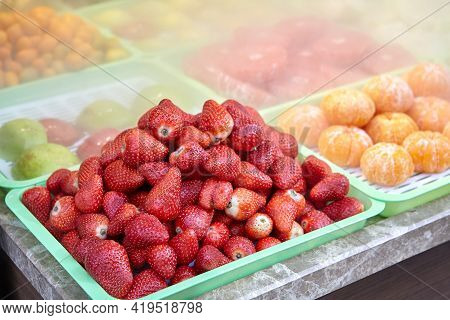 Chilled Fruits Lie In Tray On Store Counter Surrounded By Fog.