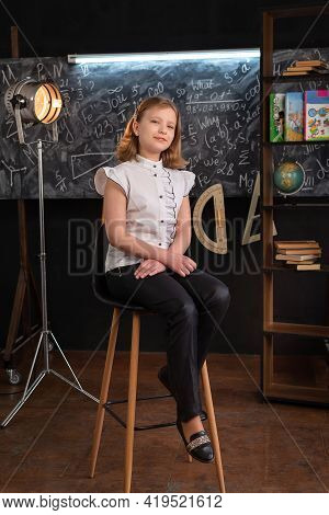 A Girl In Strict Clothes Sits On A Chair Near The School Blackboard