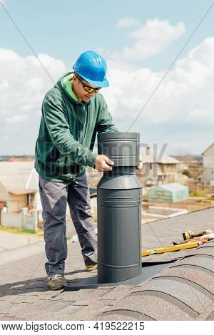 Male Worker With Blue Helmet Installs An Iron Chimney. Worker With Sunglasses Repairing Chimney On R